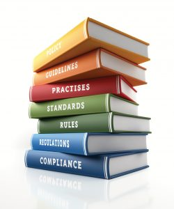 Colorful books of compliance, standards and rules are sitting on top of each other. The books have unique texts on their spines related to compliance subject. Isolated on white background. Clipping path is included. High quality 3d render with copy sapce.